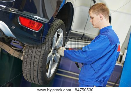 car mechanic screwing or unscrewing car wheel of lifted automobile by pneumatic wrench at repair service station poster