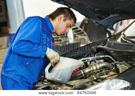 auto mechanic technician replacing and pouring motor oil into automobile engine at maintenance repair service station poster
