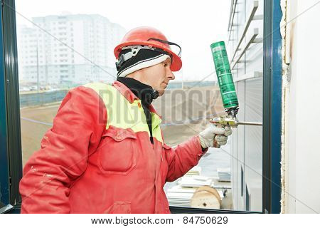 construction builder works with polyurethane foam during frame insulation at window installation