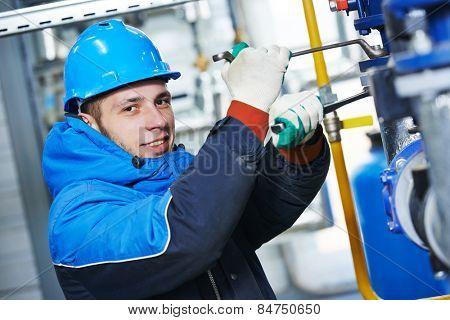 industrial heat engineer worker plumber at boiler room installation