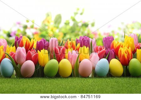 Easter eggs decorated with flowers on meadow