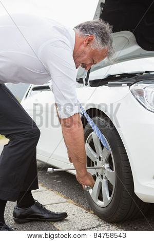 Businessman fixing tire of his car
