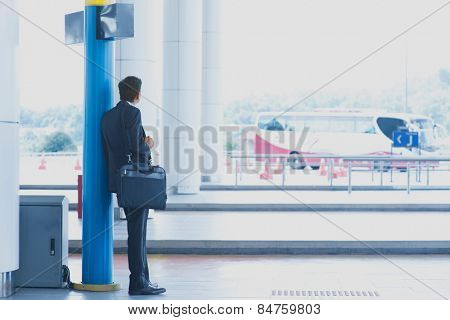 Rear view full body Asian Indian business man waiting bus at public bus station.
