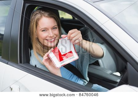Learner driver smiling and tearing l plate in her car