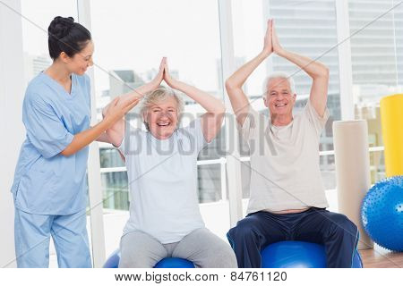 Portrait of senior couple on exercis ball being assisted by trainer in gym