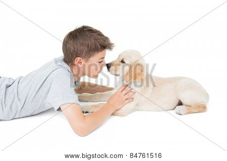 Side view of boy rubbing nose with dog over white background