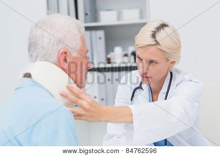 Female doctor examining senior patient wearing neck brace in clinic