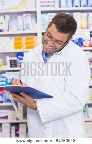 Happy pharmacist on the phone wriiting on a clipboard at the hospital pharmacy