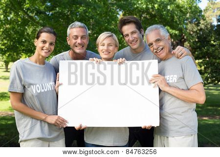 Happy volunteer family holding a blank on a sunny day
