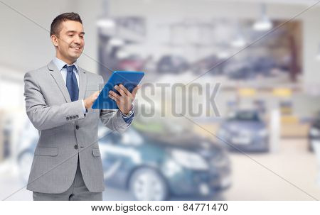 business, people, car sale and technology concept - happy smiling businessman in suit holding tablet pc computer over auto show or salon background