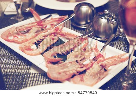 Raw scampi dish on restaurant table - tasty seafood, toned photo