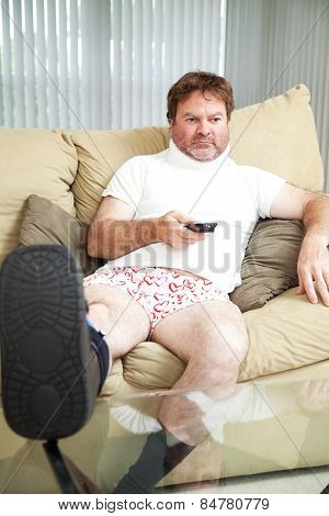 Injured man at home on the couch, wearing a foot brace and neck collar.