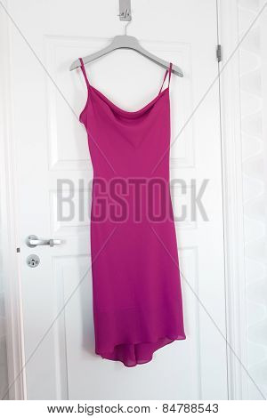 Pink Dress hanging on a door