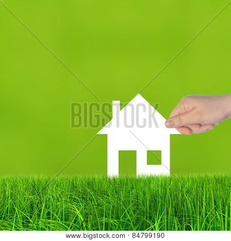 Concept or conceptual white paper house symbol held in hand by a woman in green summer grass background, metaphor to construction, eco, ecology, loan, mortgage, property, business, investment or home poster