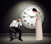 angry woman staring at lazy man on chair. photo in empty dark room with big white clock on the wall poster
