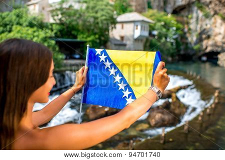 Woman with Bosnian flag in Blagaj village