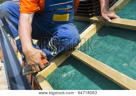 A Roofer On The Rooftop Prepairing Wooden Construction. Measuring For Better Accuracy.