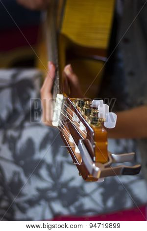 Acoustic Guitar's Fretboard Head And Girl's Hand On A Fretboard
