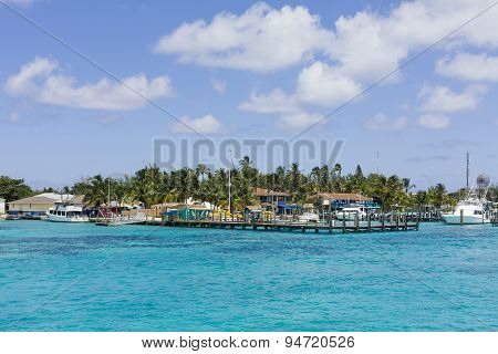 Image Of A Dock And A Few Sailing Boats Near Some Homes.