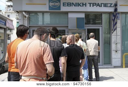 People Stand In A Queue To Use The Atms Of A Bank