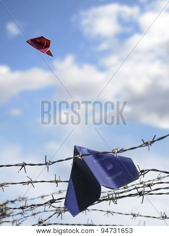 Refugee Passport Hangs In Barbed Wire, An European Passport Flies In The Blue Sky