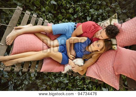 Young Couple Relaxing On A Garden Hammock