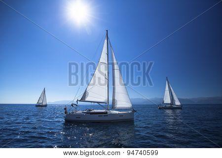 Sailing ship yachts with white sails in the open Sea. Noon, the blue sky and the Sun at the Zenith.