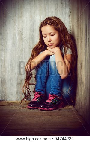 Portrait of a sad girl child sitting in the corner of the room. Loneliness, depression. Awkward age.