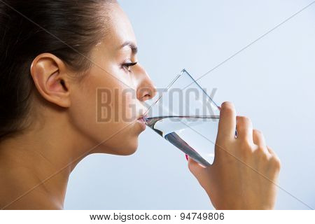 Close-up of pretty young woman drinking water from glass