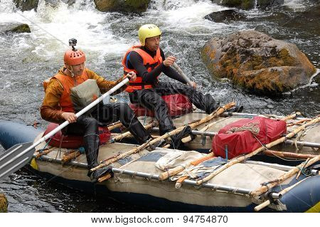 Two men on a makeshift catamaran raft on the northern river.