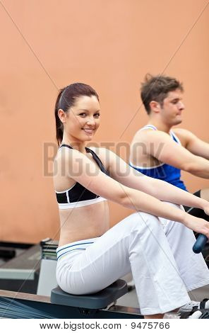 Athletic Young People Using A Rower In A Fitness Center