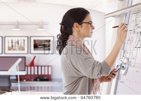 Focused casual caucasian female architect working at drawing board with pen in hand. Wearing glasses, at office. Floor plan, busy, concentration, unsmiling. poster