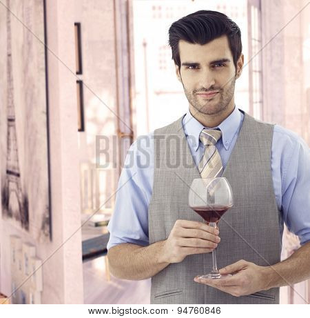 Handsome elegant young caucasian man with glass of wine at Paris retro home. Smiling standing, bristly, looking at camera. Suit and tie. Copyspace.