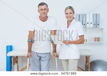 Doctor and patient with crunch looking at camera in medical office