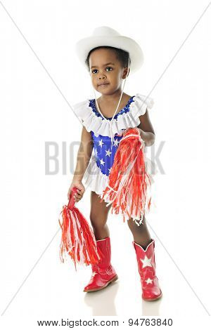 An adorable 2 year old cheerleader in a star studded red, white and blue western outfit, with a pom-pom in each hand.  On a white background.
