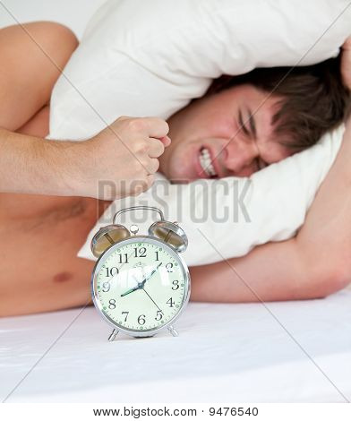 Angry Man Stressed By His Alarm Clock Lying On His Bed