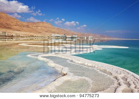 Israeli coast of the Dead Sea. Path from the salt winds picturesquely in salt water. Hotels on the bank are reflected in smooth water