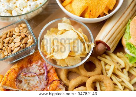 fast food and unhealthy eating concept - close up of different fast food snacks on wooden table poster