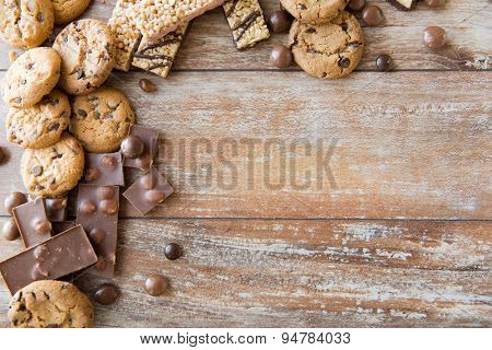 junk food, sweets and unhealthy eating concept - close up of candies, chocolate, muesli and cookies on plate