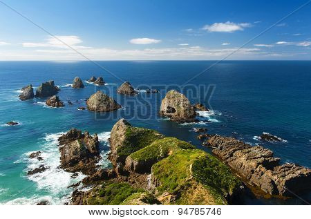 Nugget Point is located in the Catlins area on the Southern Coast of New Zealand, Otago region. The area is famous for many rock islands - nuggets - in the sea.