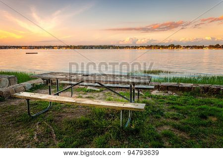 Picnic Table On Grass Harbor At Sunset poster