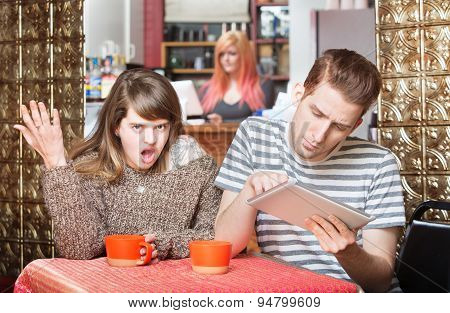 Insulted Woman Next To Man On Tablet