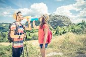 Couple of hikers on an excursion in the nature - Tourists having a pause while on a trekking tour - Two youung sportive tourists having a walk in the countryside poster