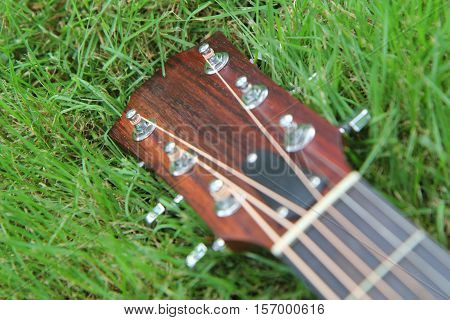 headstock of acoustic guitar on grass on the grass field