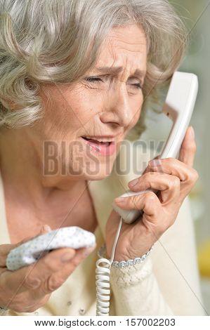 Portrait of upset senior woman holding handkerchief talking on the phone