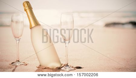 Champagne flutes with bottle on sand at beach