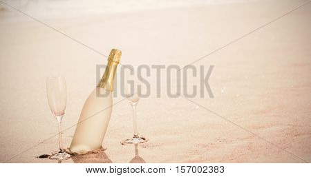 Champagne flutes with bottle on sand at beach during sunny day