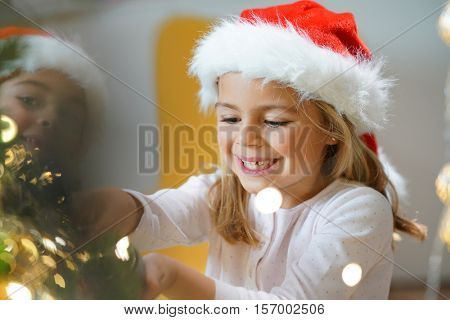 Portrait of cute little girl decorating Christmas tree