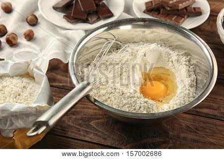 Ingredients for making chocolate cake on wooden background