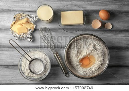 Ingredients for making cake on grey wooden background, top view
